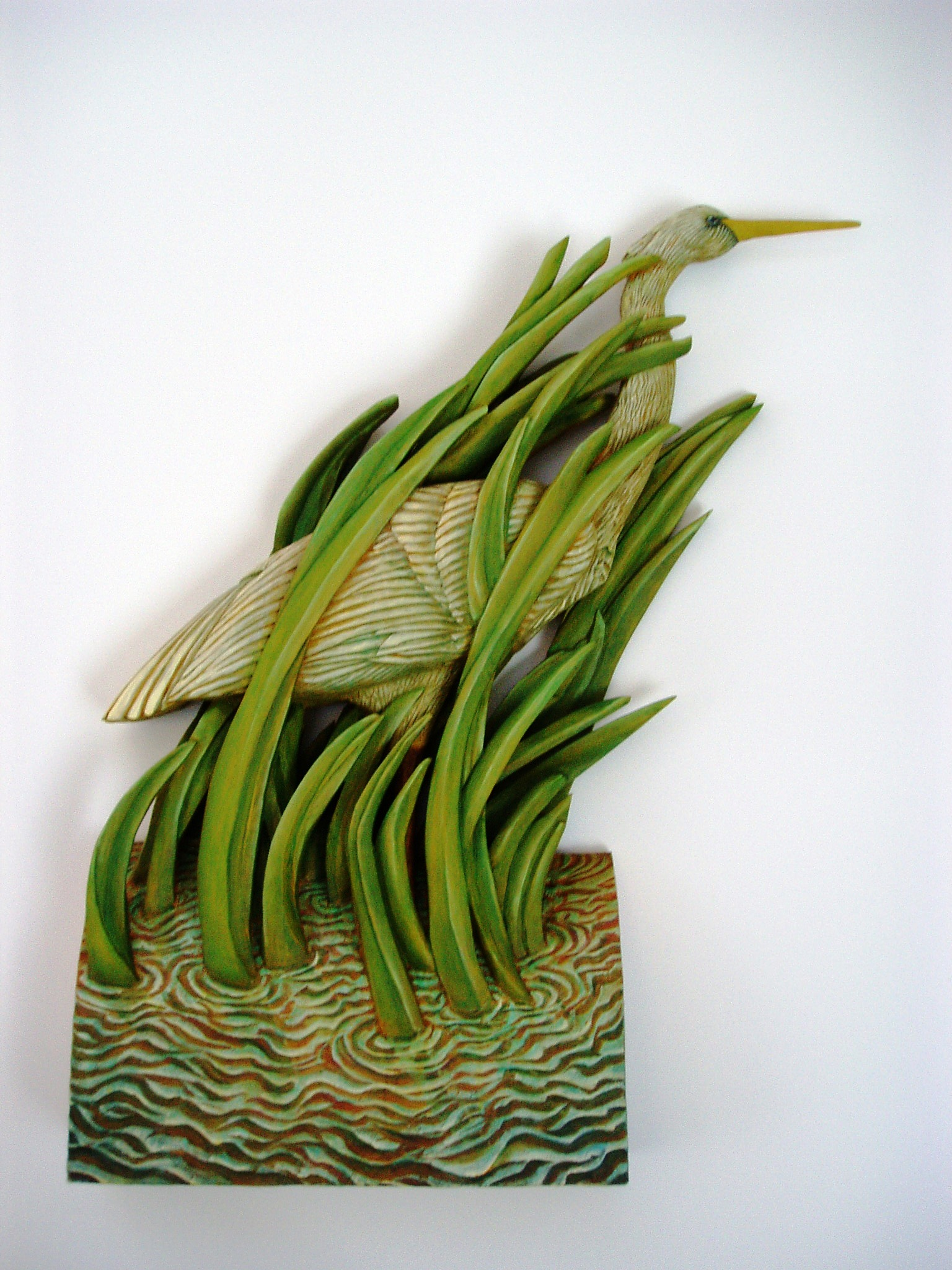 image of Large Wading Heron painted on carved, layered basswood depicts a heron wading amongst green reeds growing from a rippled block of water